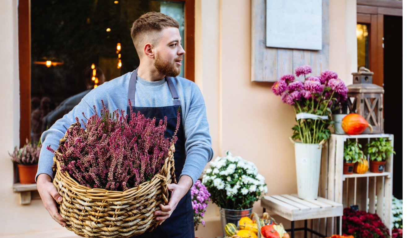 Small Business employee carrying a basket of flowers outside a storefront with other flowers being displayed